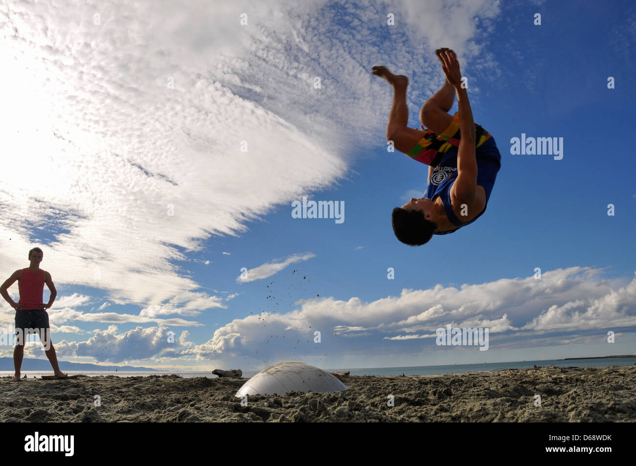 Young man somersaulting on the beach. Photographed in Nelson New Zealand. Model Re1lease Availanle Stock Photo