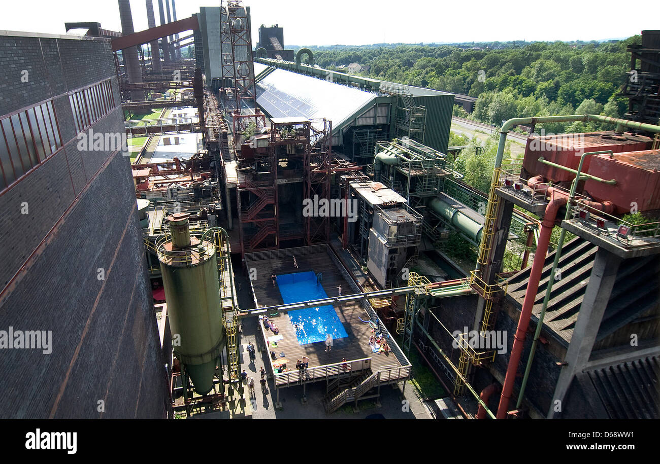 Swimmers visit the swimming pool at the former coal mine 'Zollverein' and enjoy one of the first sunny days - Stock Image