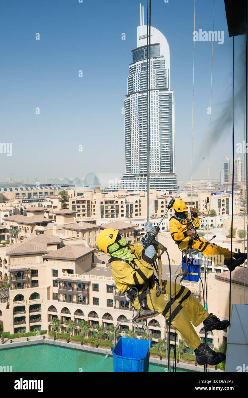 Window cleaners abseiling down high-rise apartment building in Dubai United Arab Emirates Stock Photo