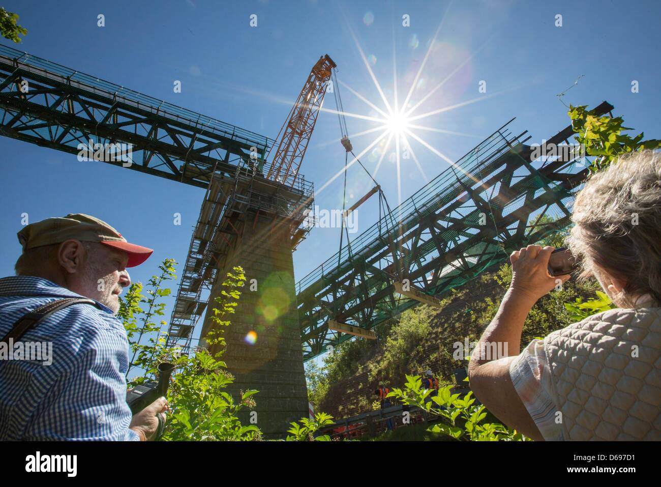 Visitors watch a big crane lift an 80 t-part of the railway viaduct in Angelroda, Germany, 28 June 2012. It is the - Stock Image