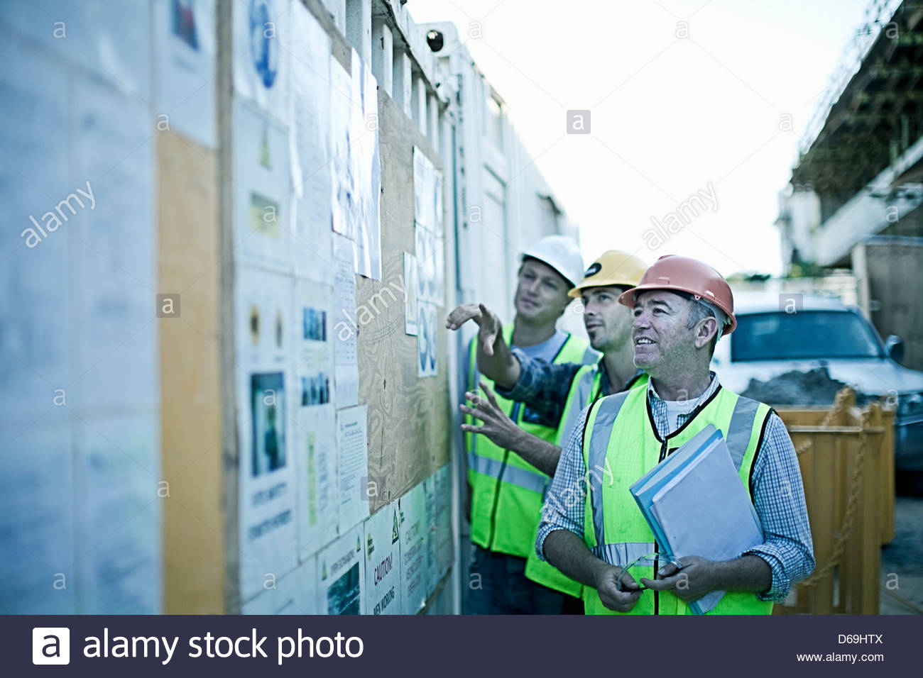 Construction worker reading boards - Stock Image