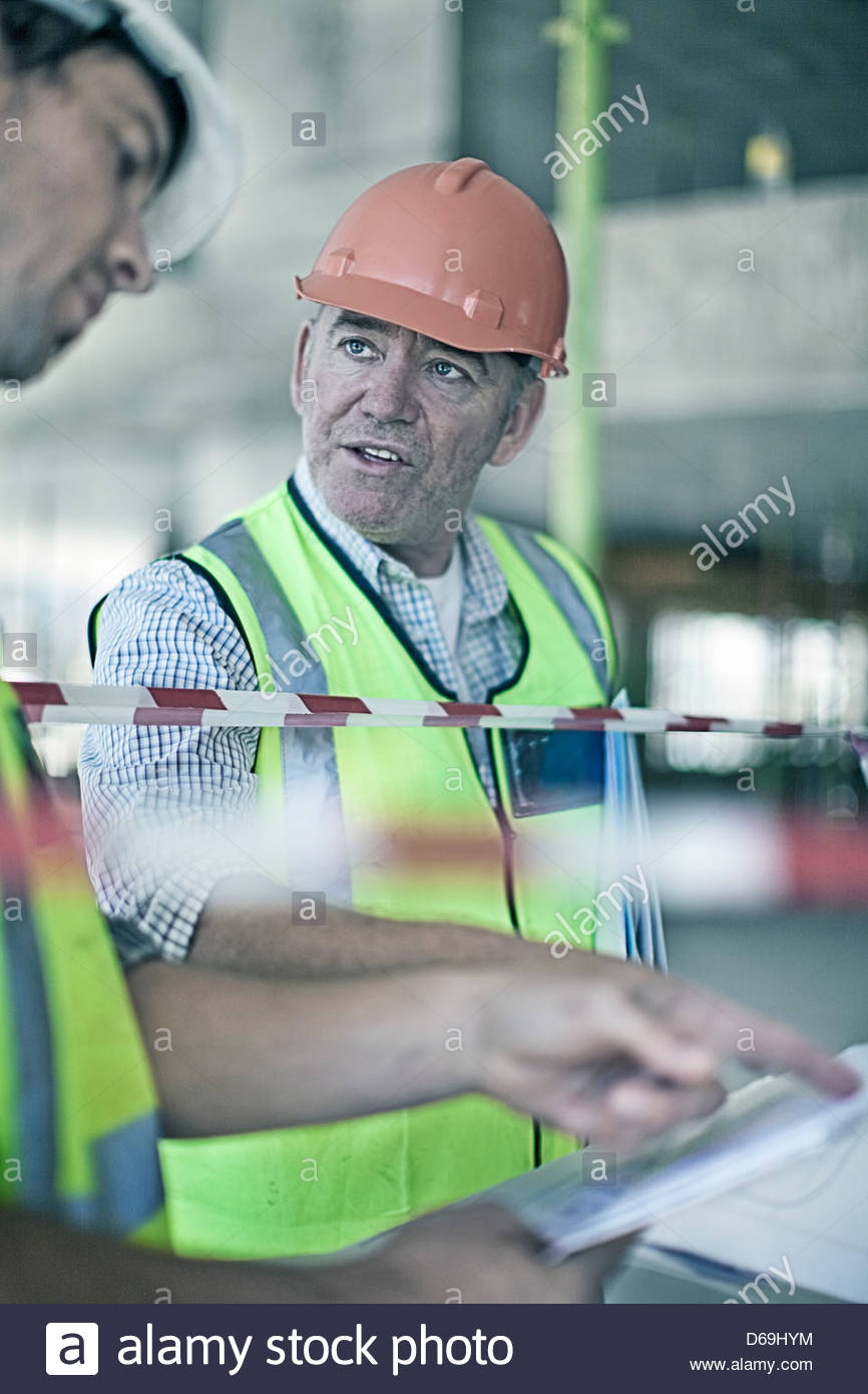 Construction workers reading blueprints - Stock Image