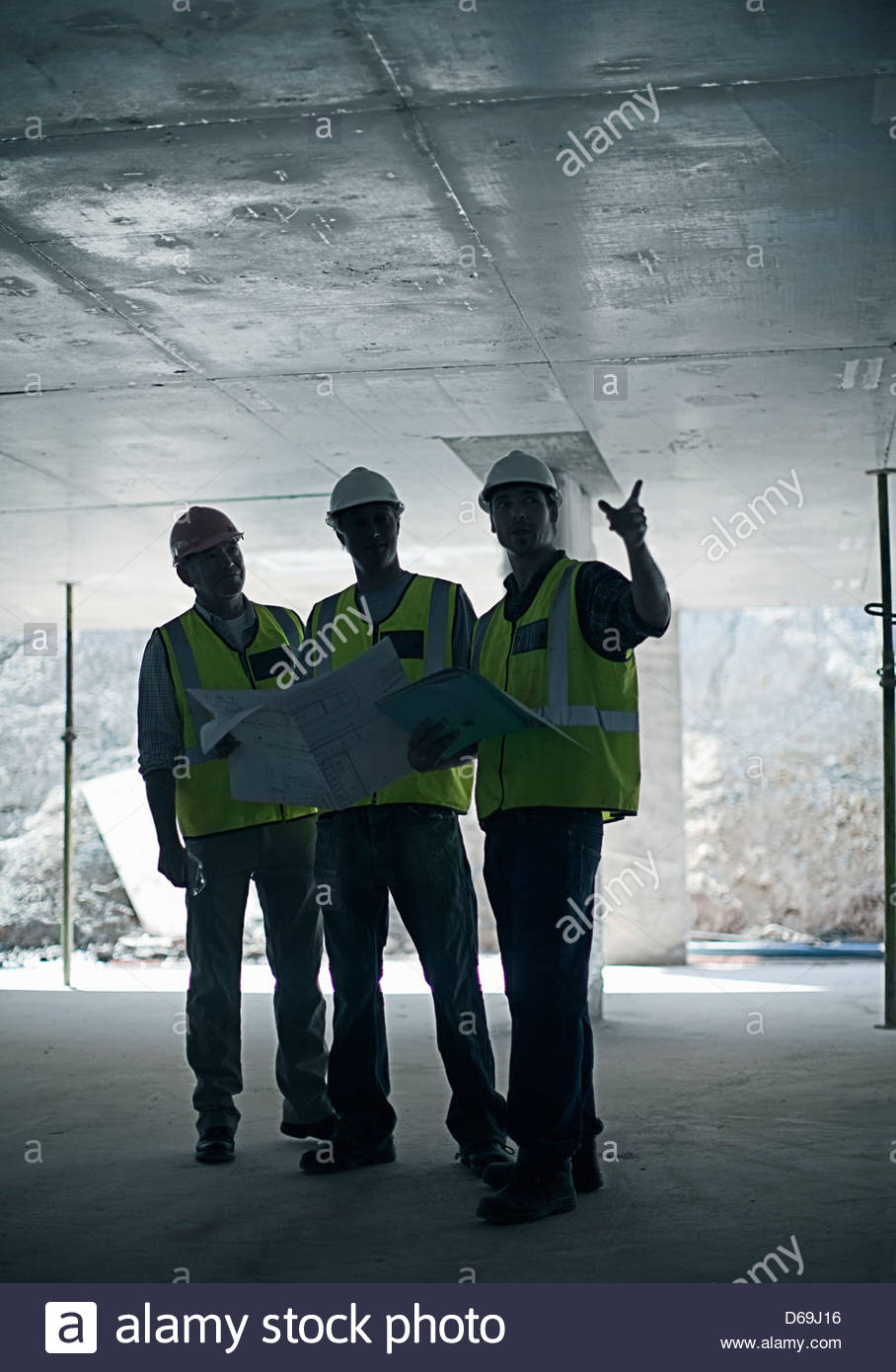 Construction workers using blueprints Stock Photo