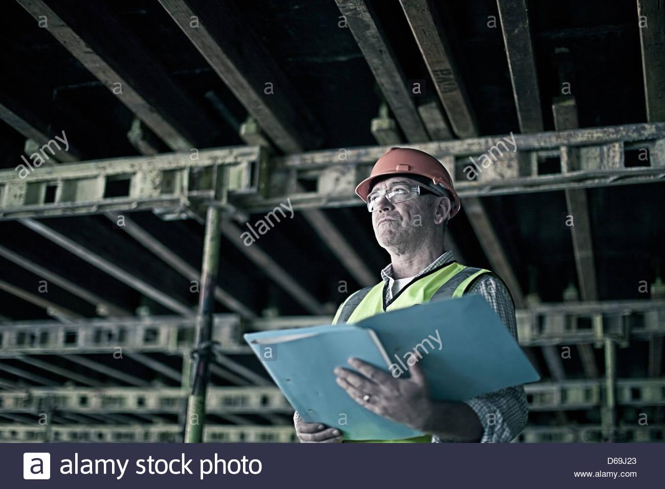 Construction worker reading blueprints - Stock Image