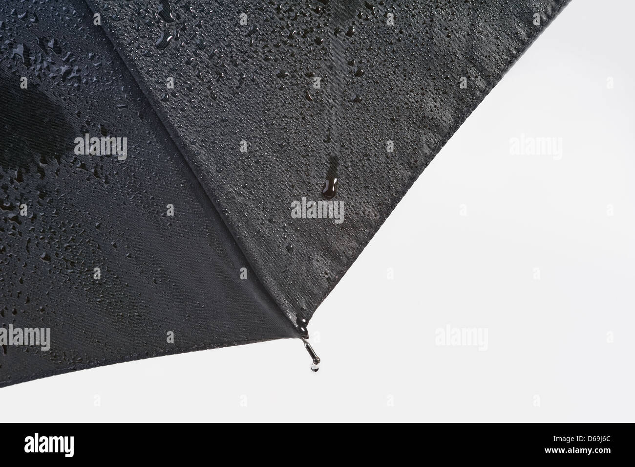 Section of an umbrella with rain drops. - Stock Image
