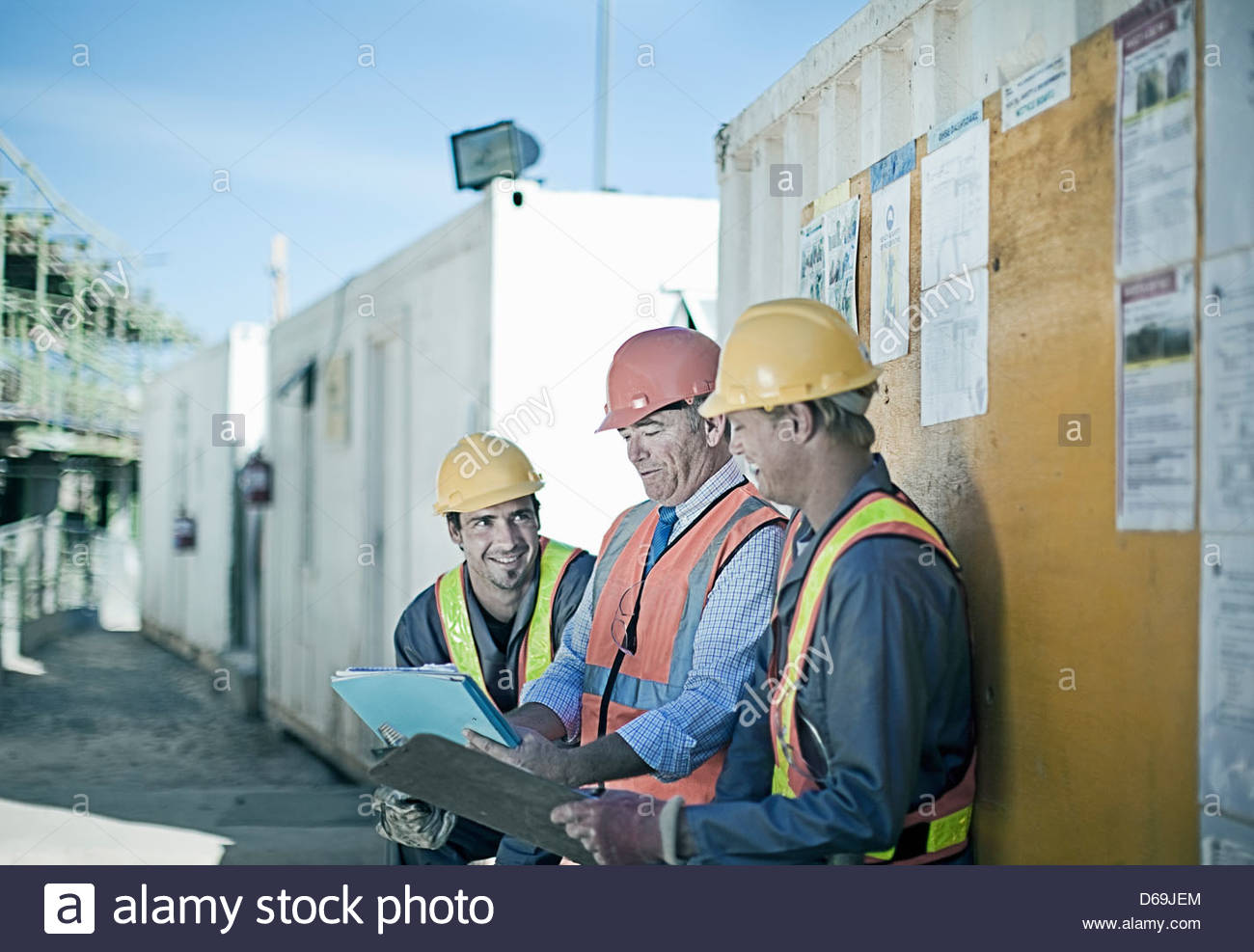 Workers and businessman on site - Stock Image