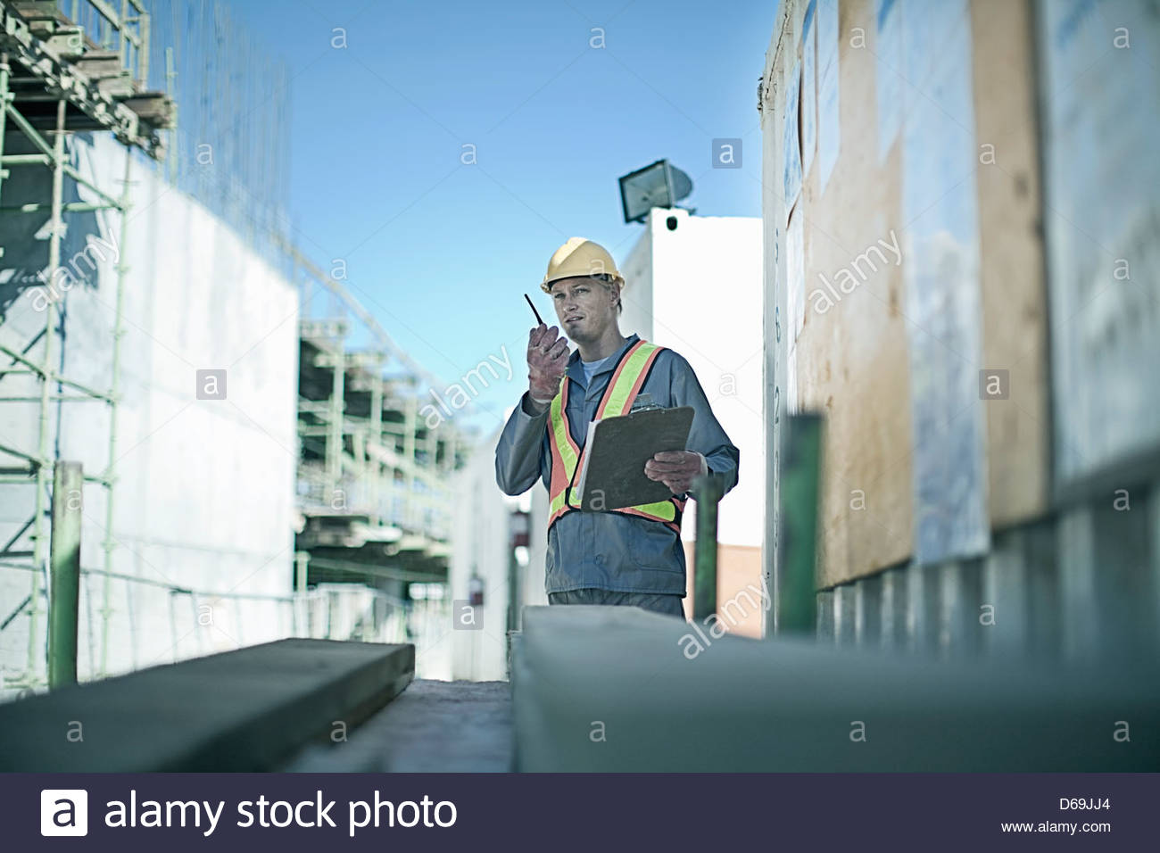 Construction worker using walkie talkie - Stock Image