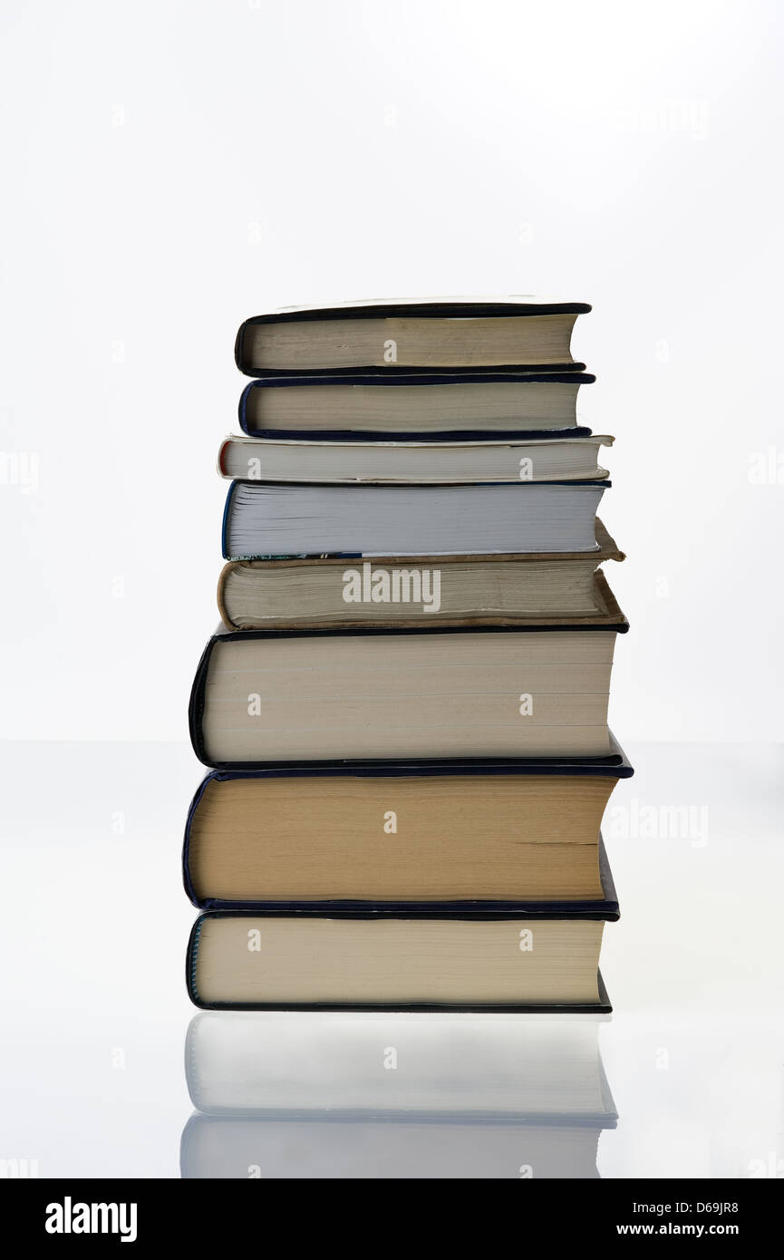 A stack of books on a white background. - Stock Image