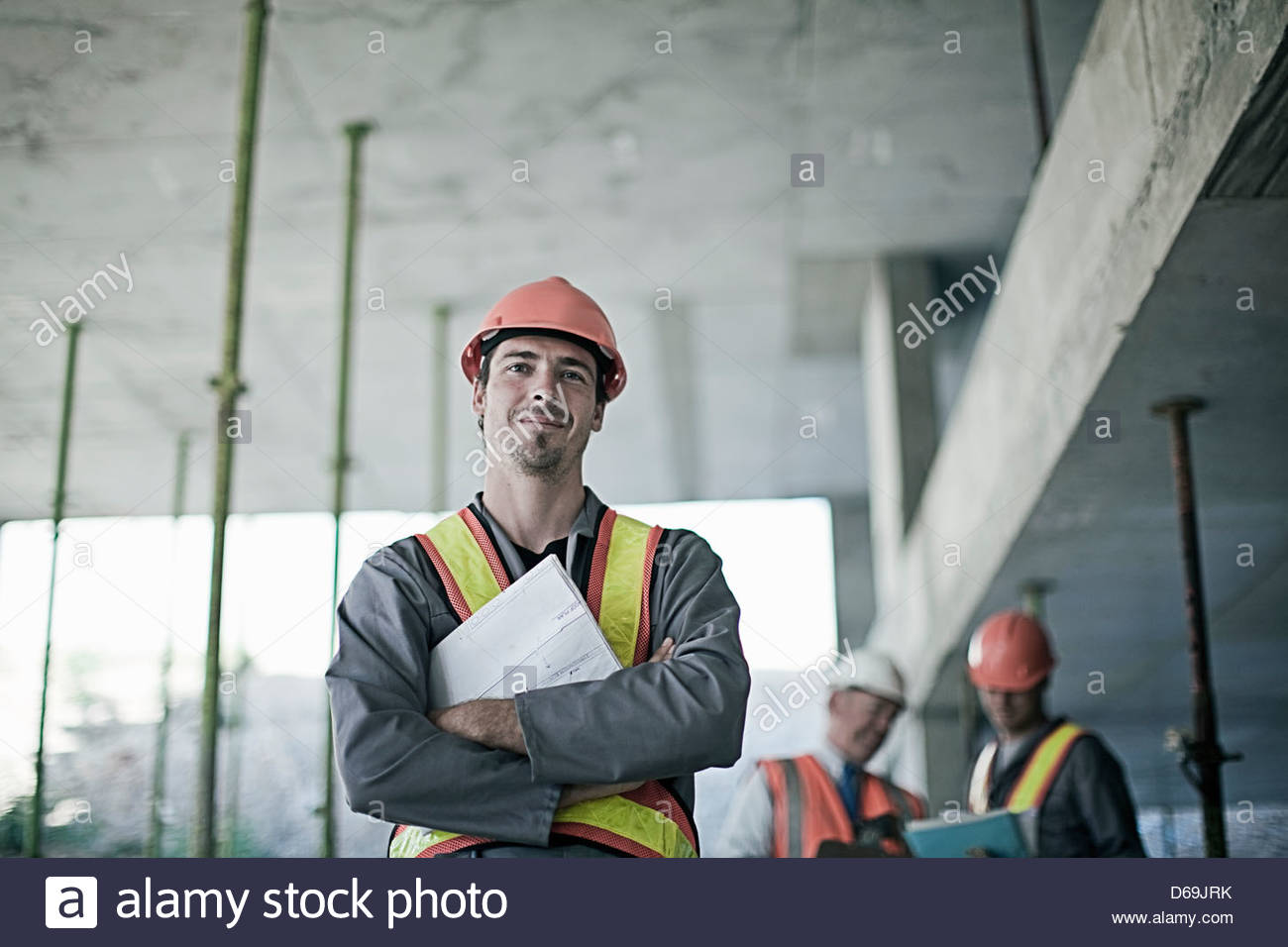 Construction worker smiling on site - Stock Image
