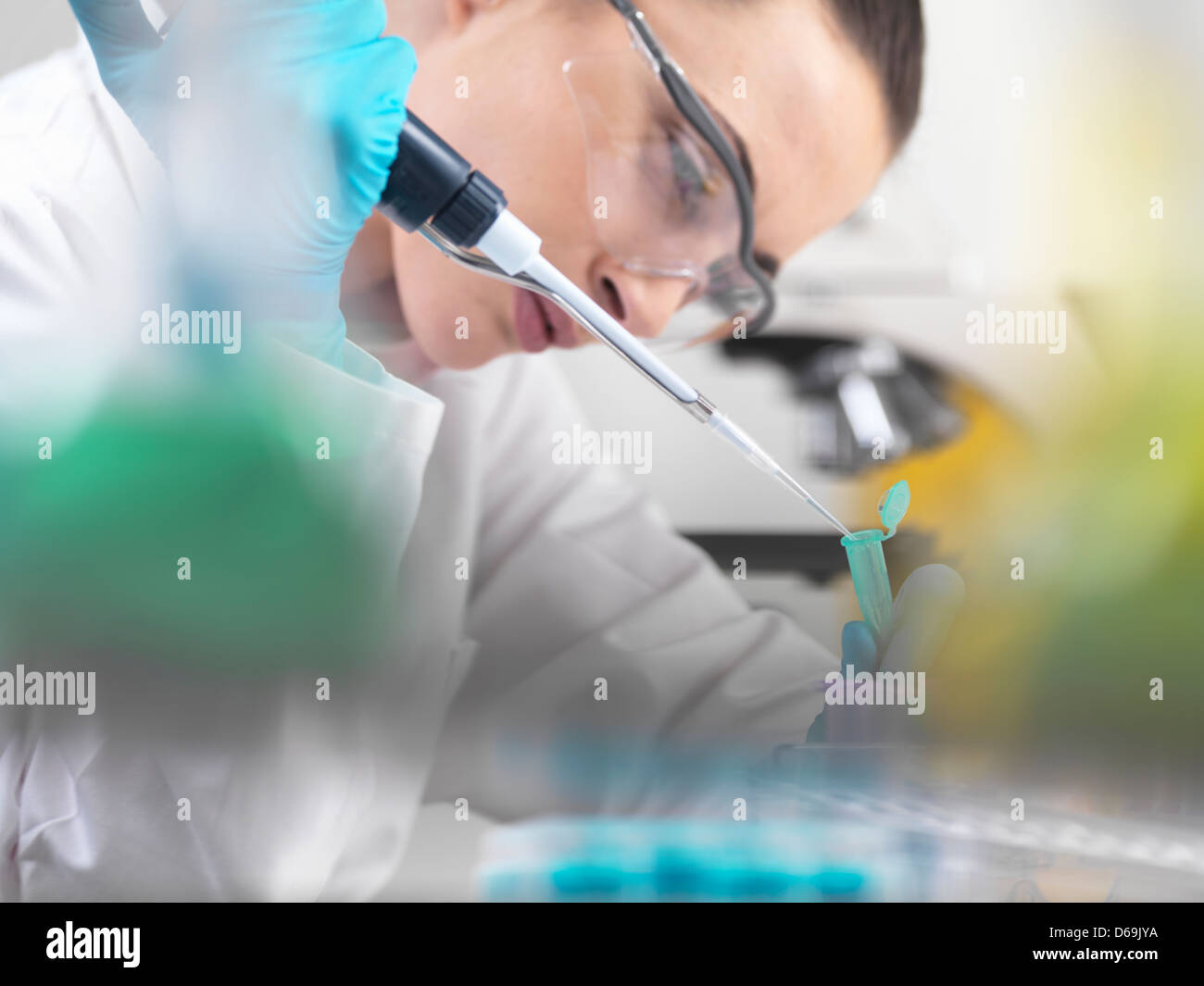 Scientist pipetting DNA sample in tubes - Stock Image