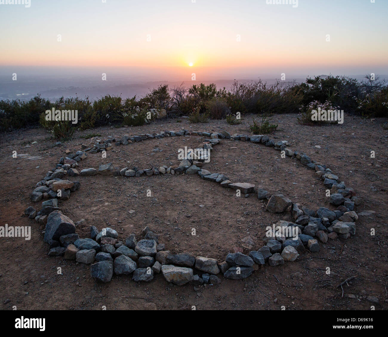 Rocks in peace symbol on cliff - Stock Image