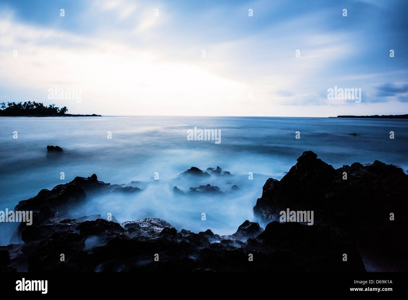 Fog rolling on rocky beach - Stock Image