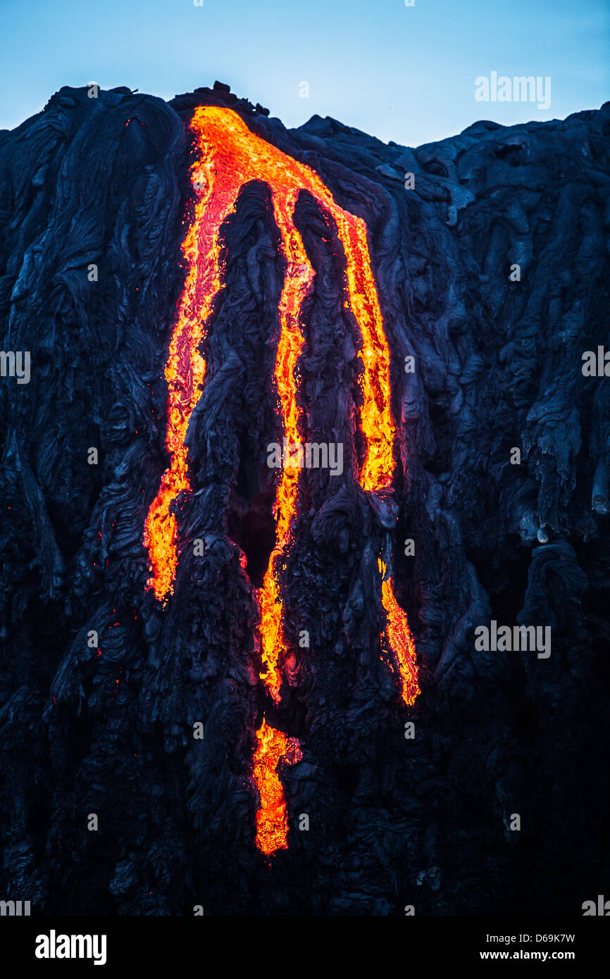 Lava flowing down rocky cliff - Stock Image