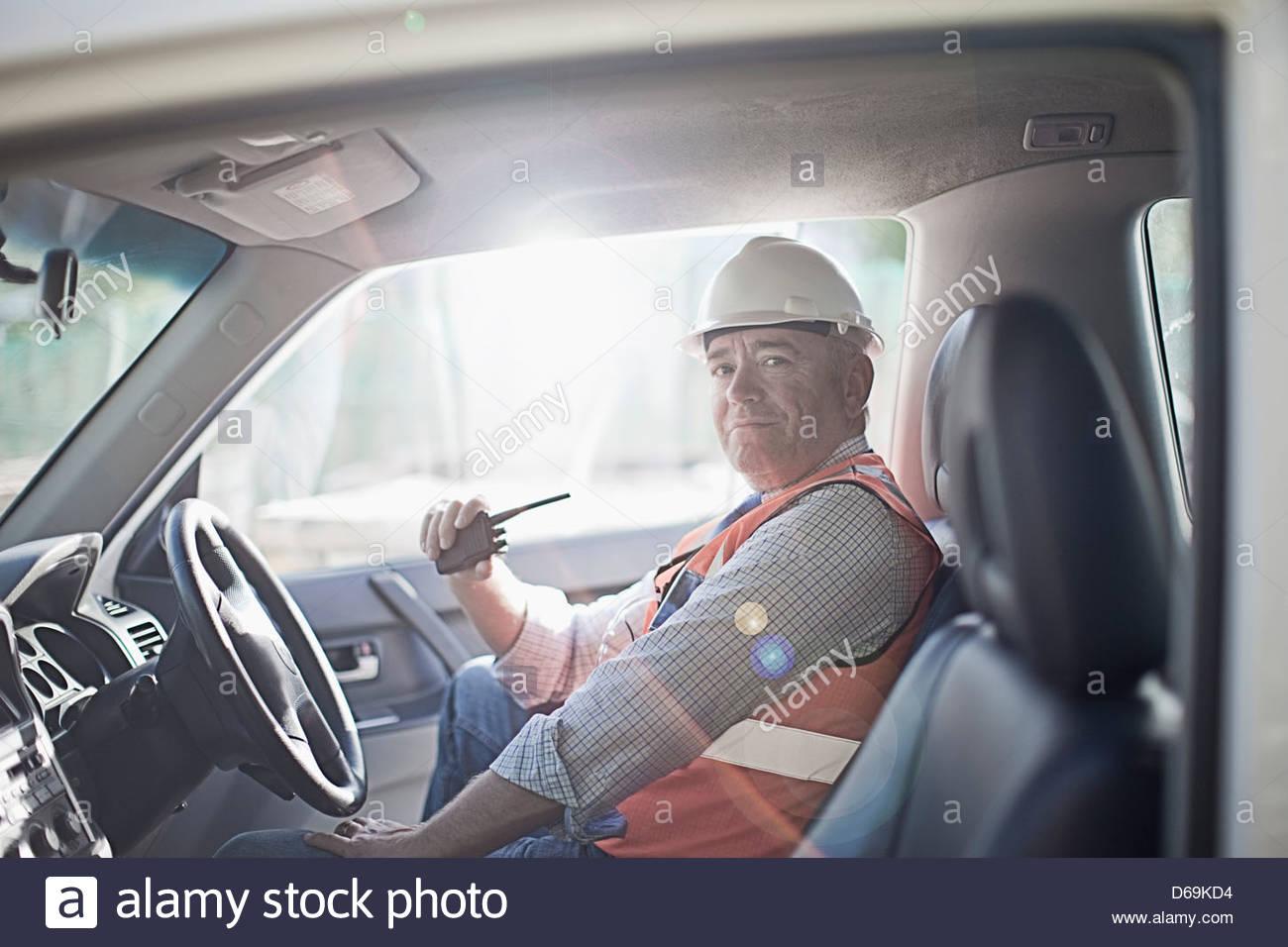 Businessman using walkie talkie in car - Stock Image