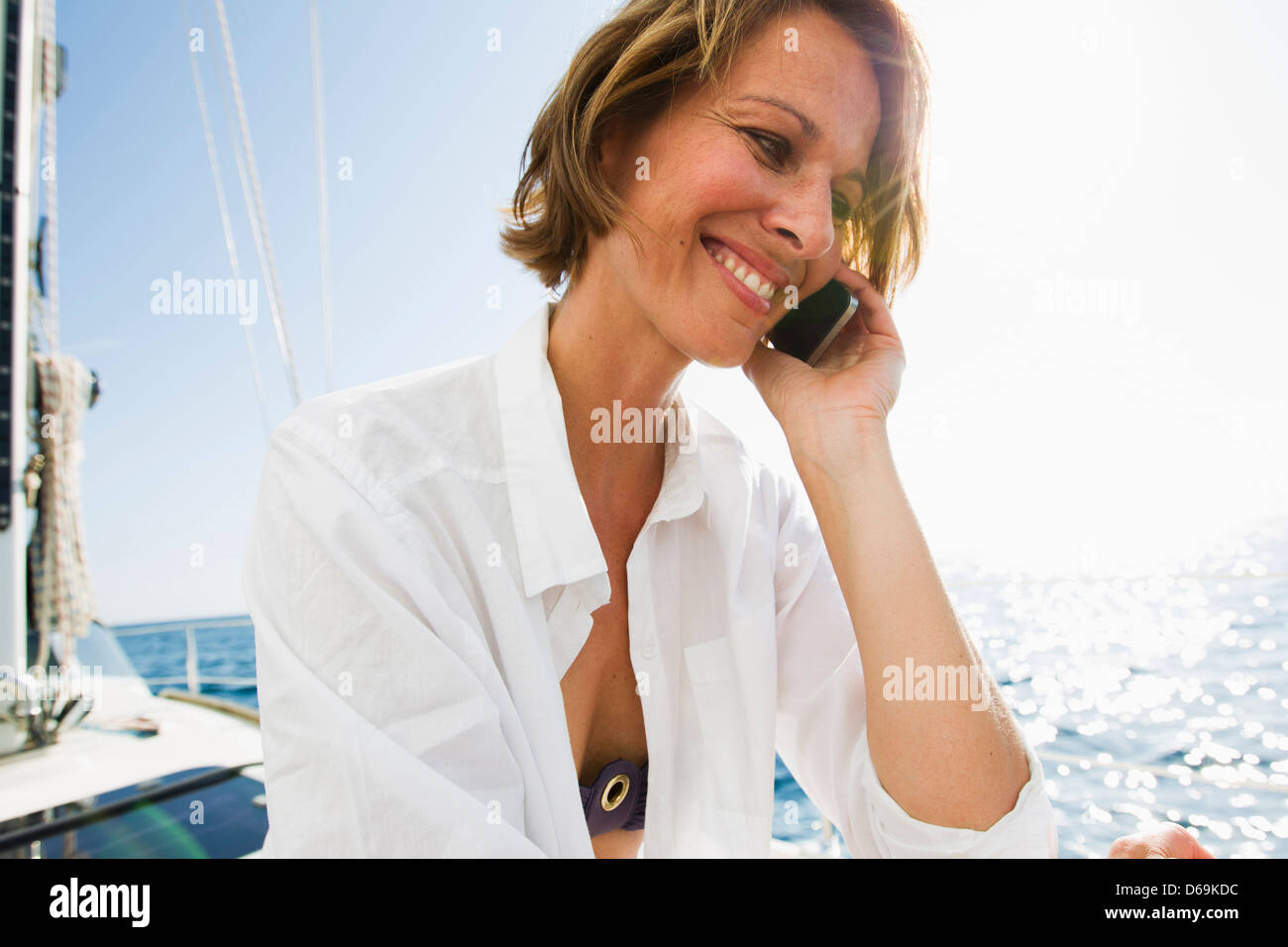 Woman talking on cell phone on boat - Stock Image