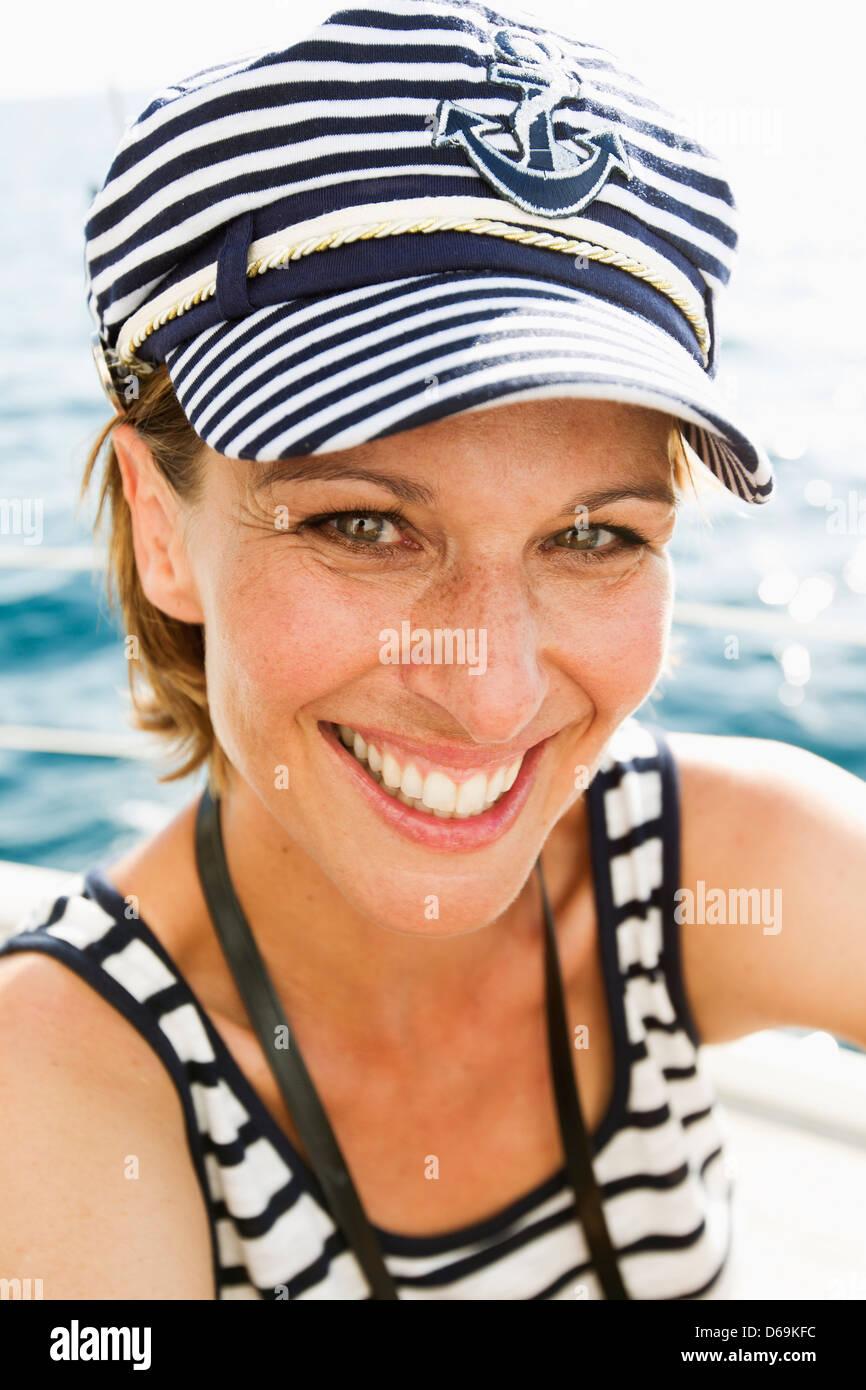 Woman wearing nautical hat and shirt - Stock Image