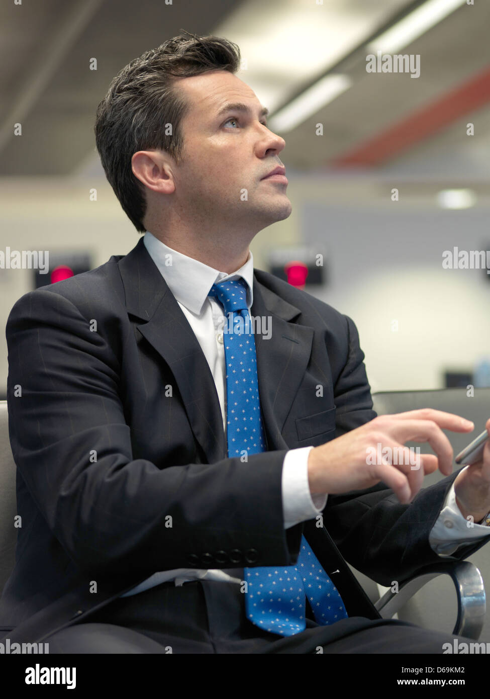 Businessman using cell phone in airport - Stock Image