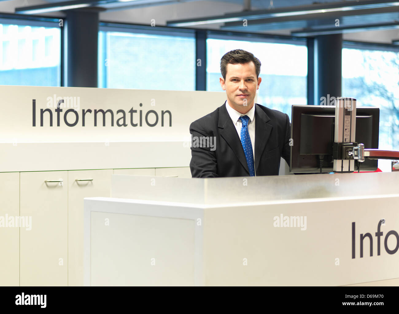 Receptionist smiling at information desk - Stock Image
