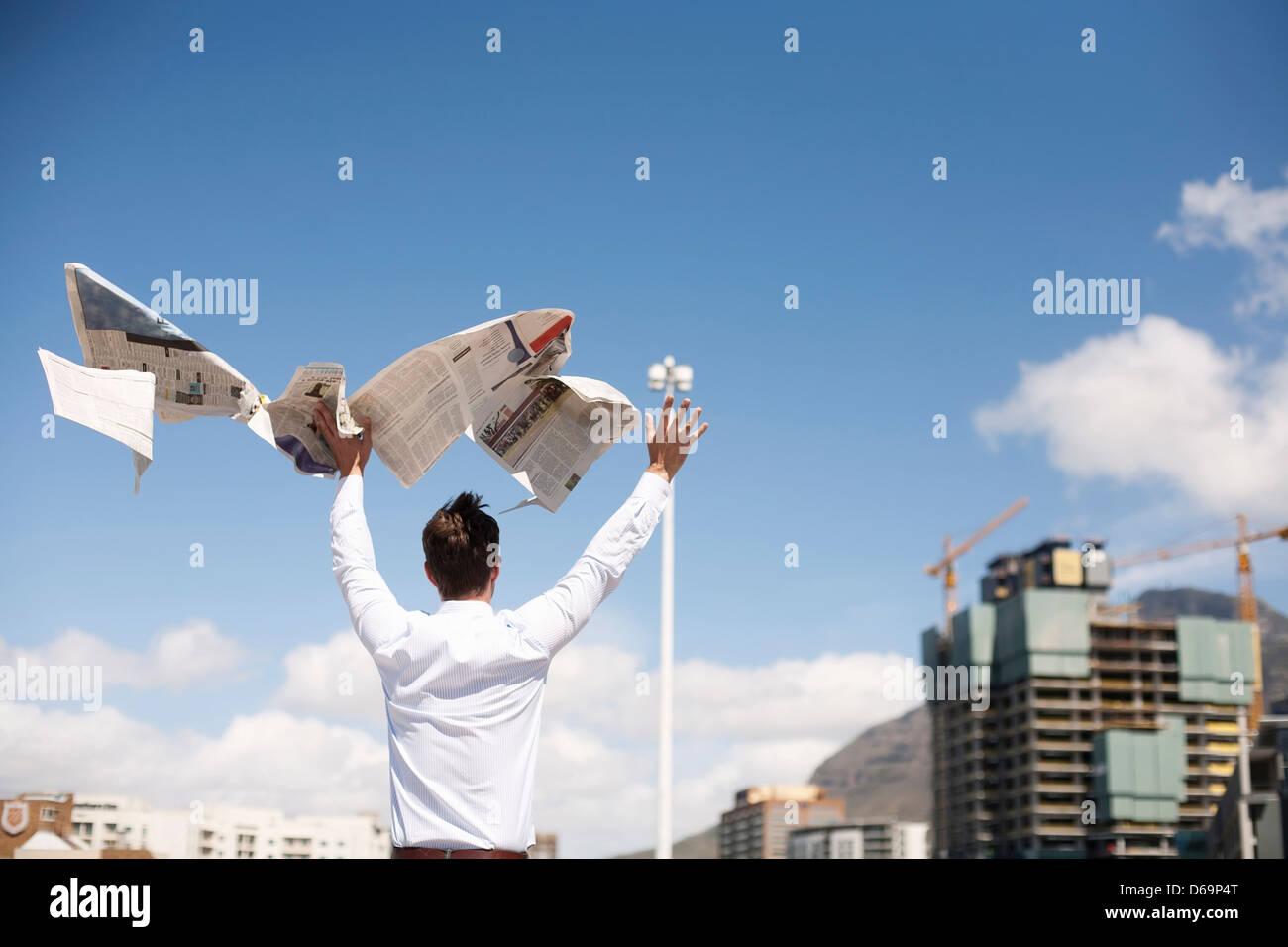 Businessman throwing newspaper in air - Stock Image