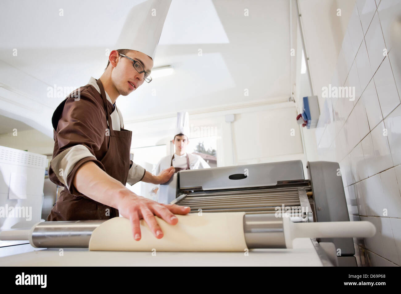 Baker rolling dough in kitchen - Stock Image