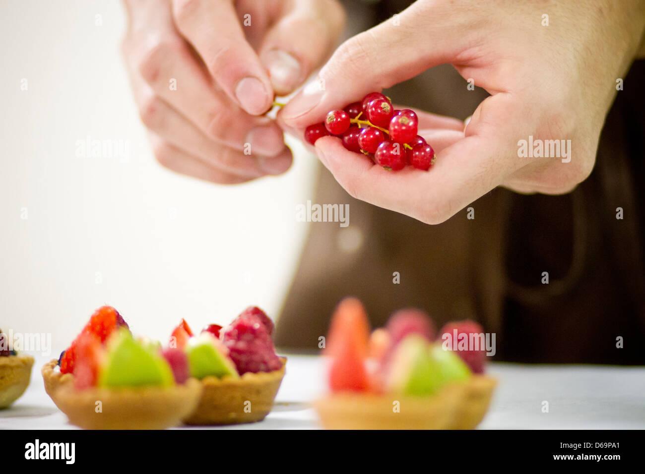 Baker making fruit tarts in kitchen Stock Photo