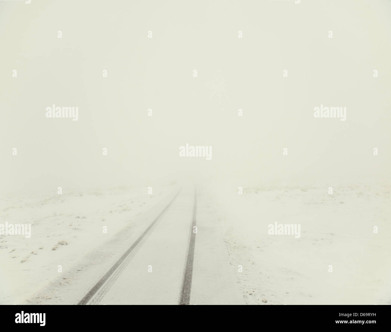 Tracks on rural road hidden by snow - Stock Image