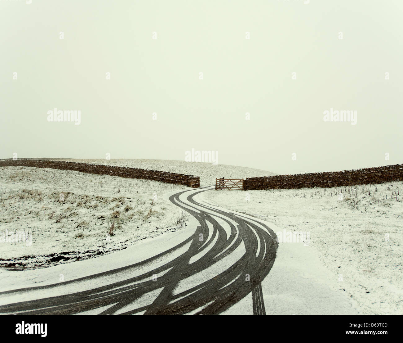 Tracks in snowy gate and driveway - Stock Image