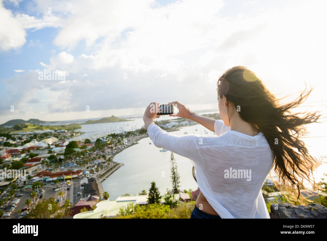 Woman taking picture of coast landscape Stock Photo