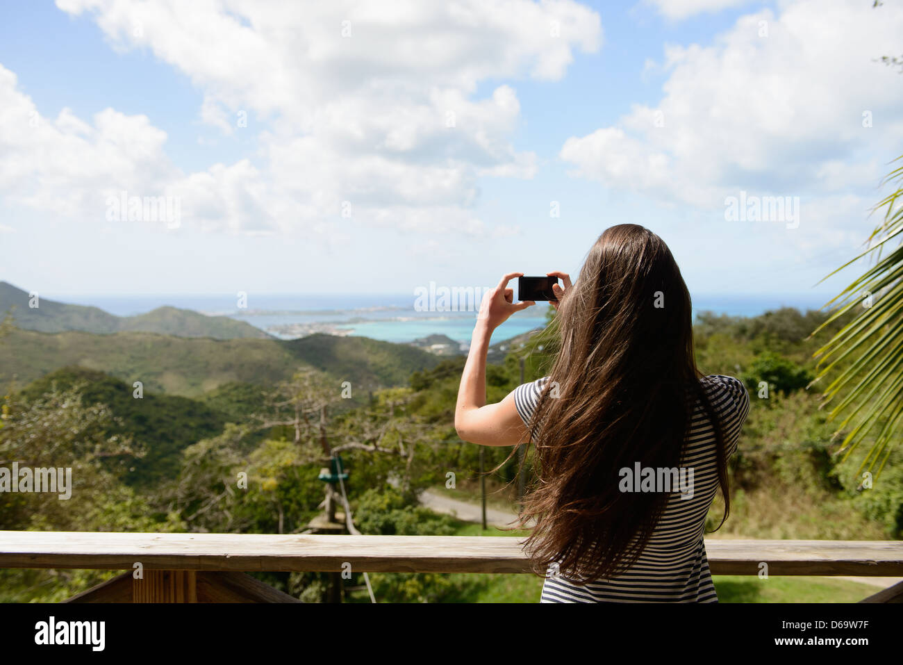 Woman taking picture of coast landscape - Stock Image