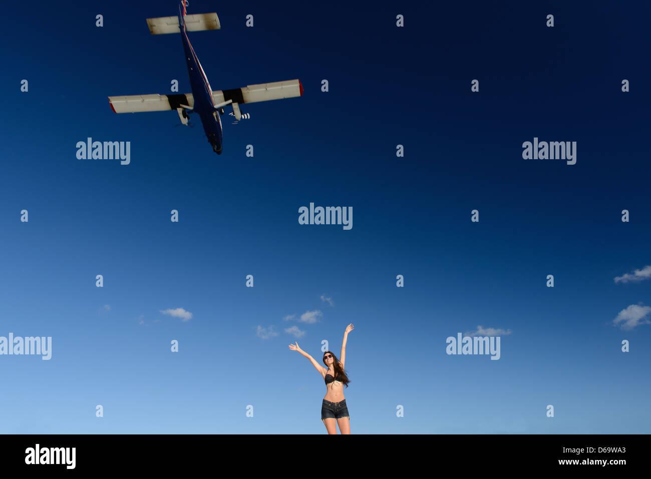 Woman in bikini greeting airplane - Stock Image