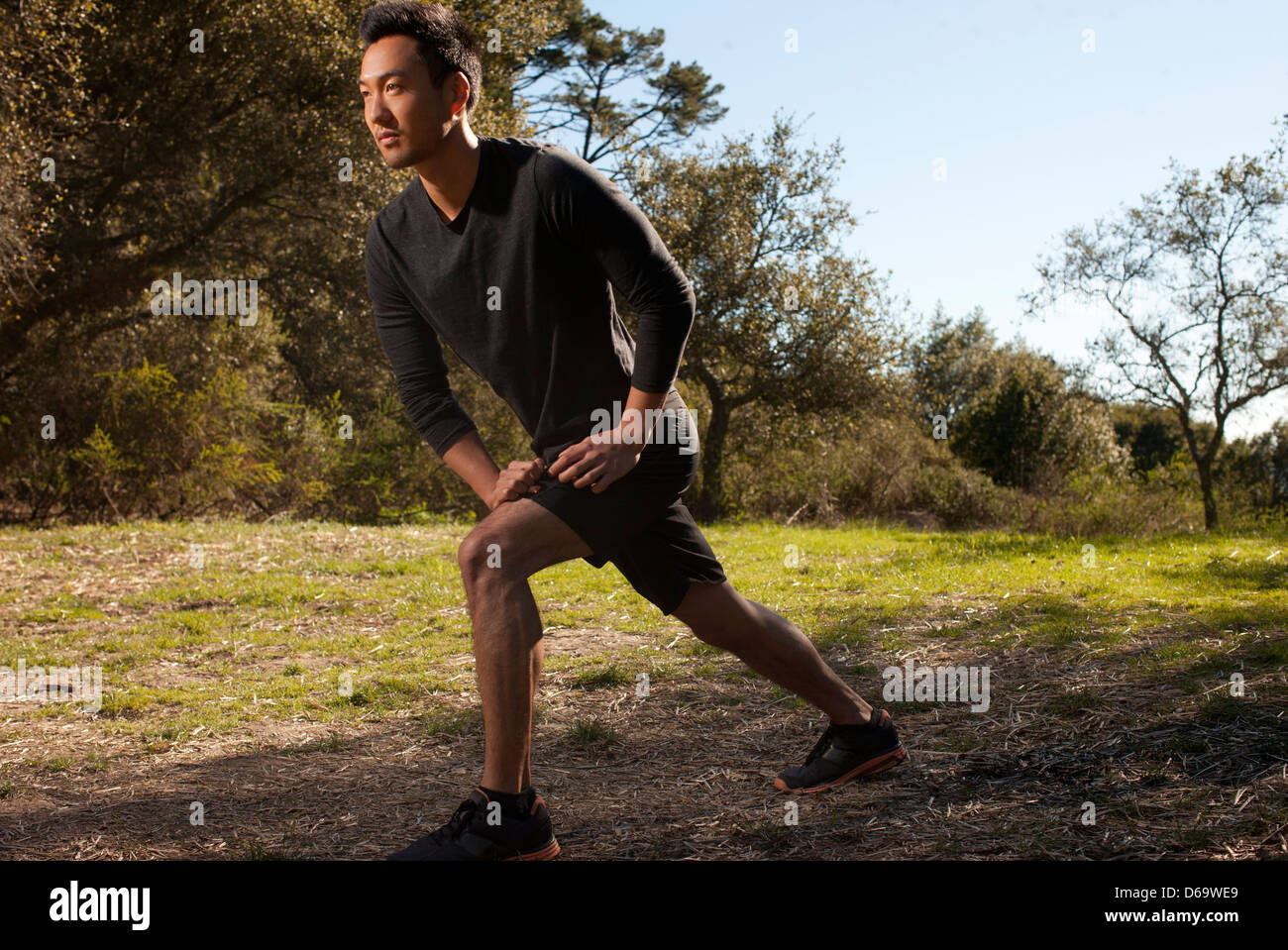 Runner stretching in park - Stock Image