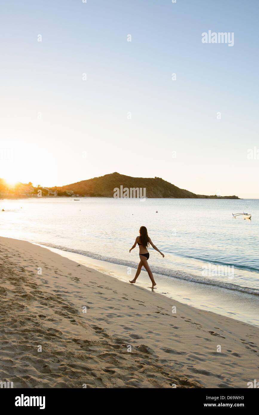 Woman in bikini walking on beach - Stock Image