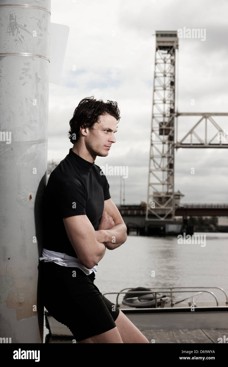 Runner standing on urban waterfront - Stock Image