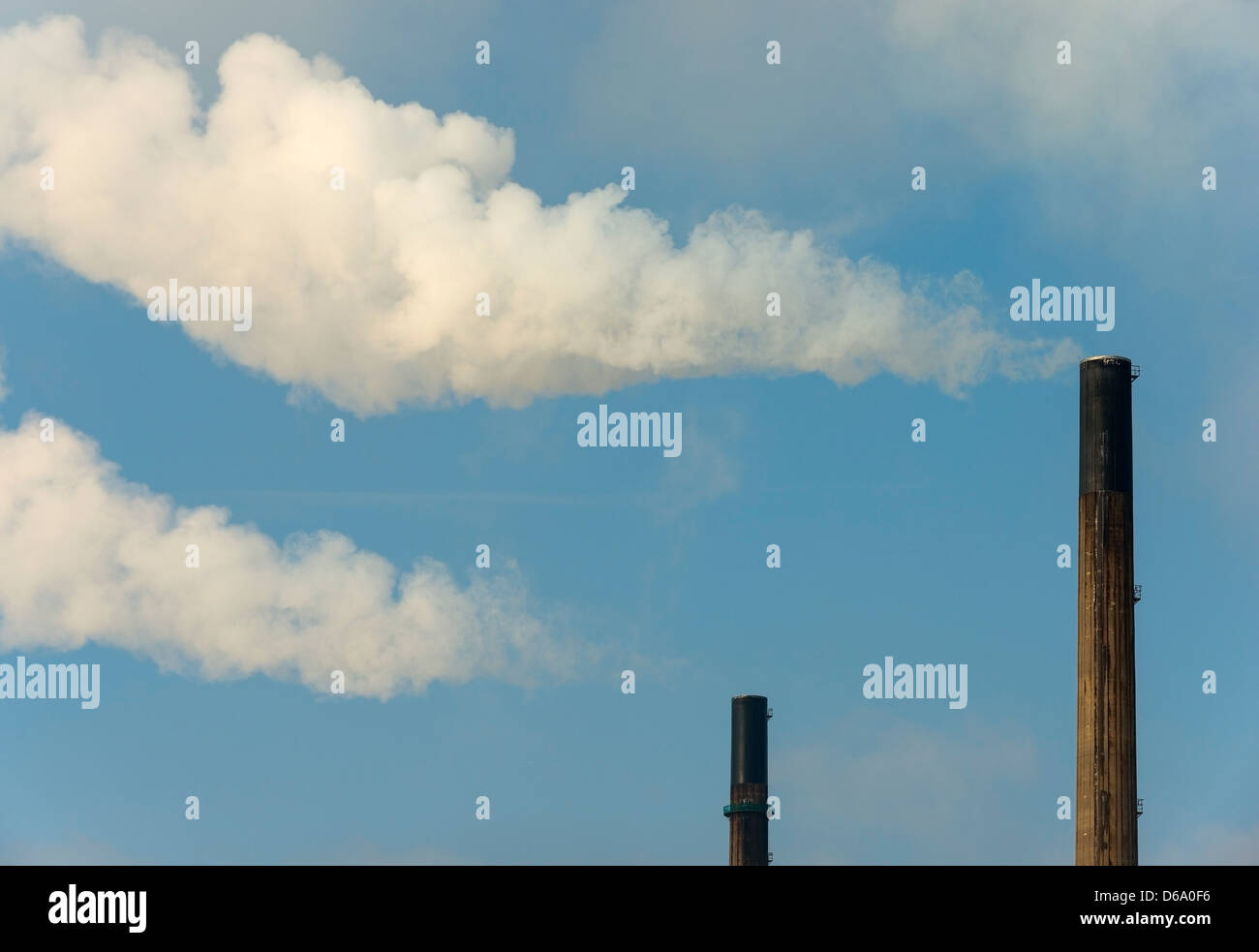 Smoke billowing from industrial chimneys - Stock Image