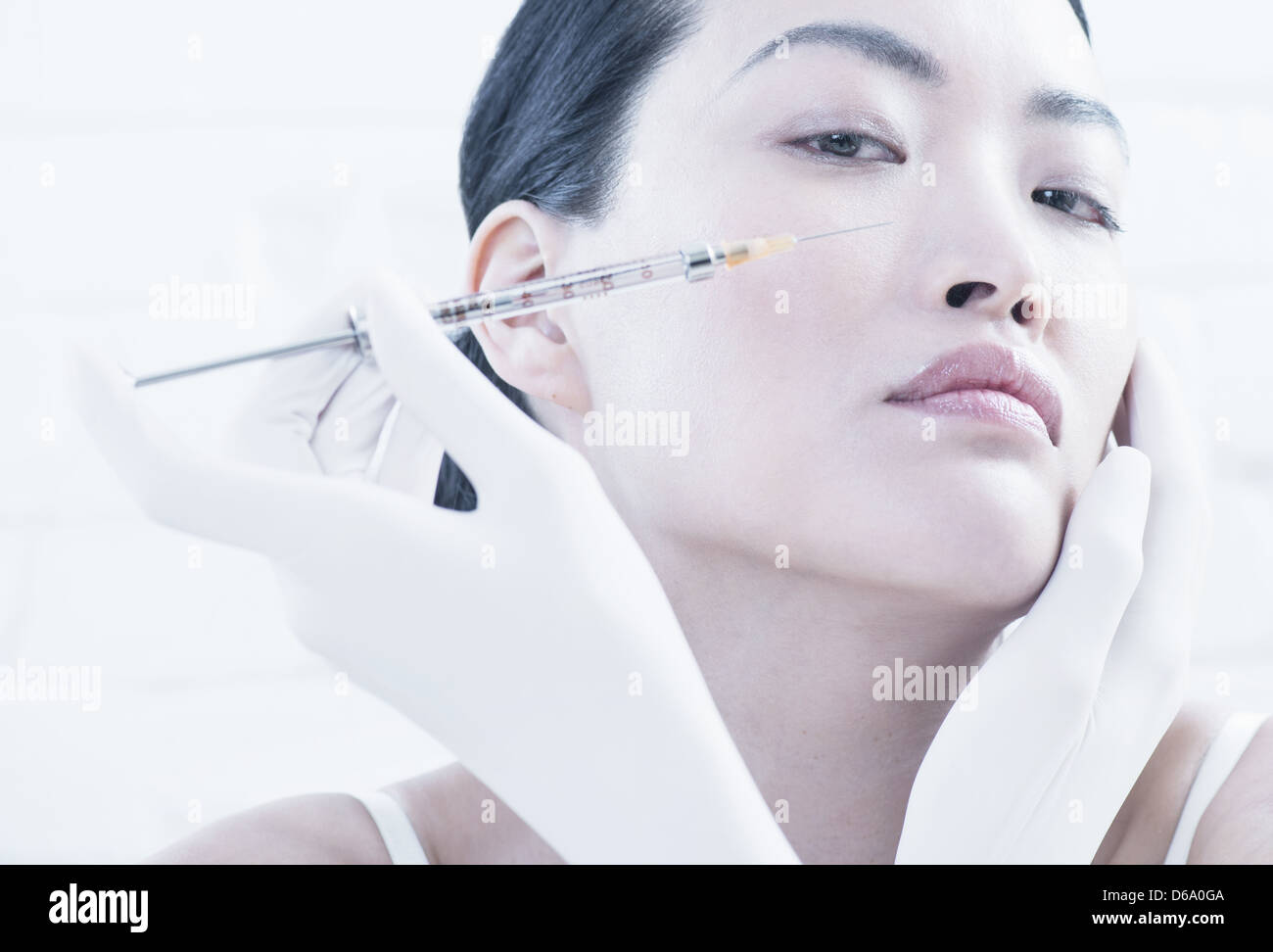Woman having Botox injection in face - Stock Image