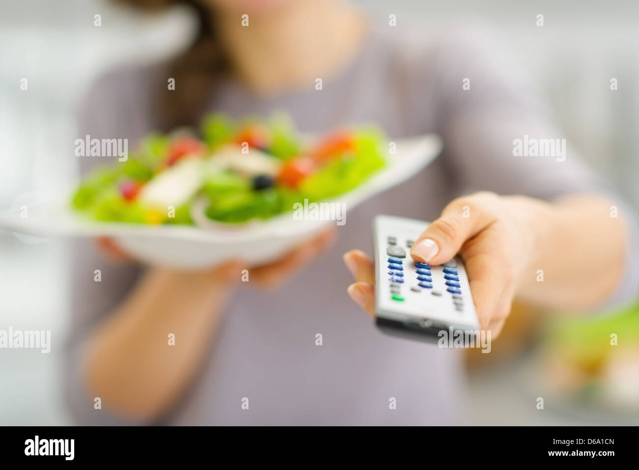 Closeup on tv remote control and fresh salad in hand of young woman - Stock Image