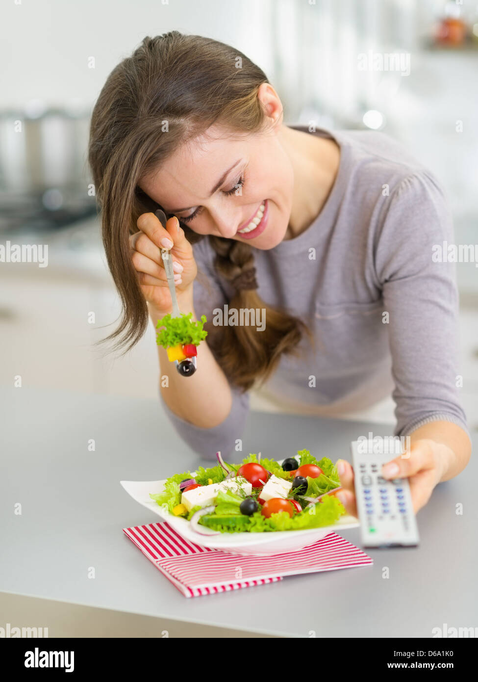 Laughing young woman eating salad and watching tv in kitchen - Stock Image