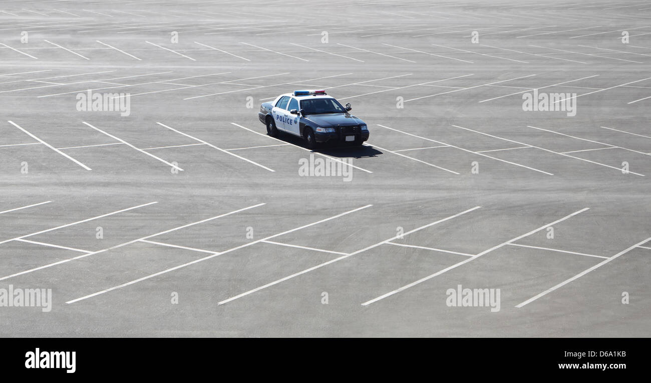 Police car parked in empty lot - Stock Image