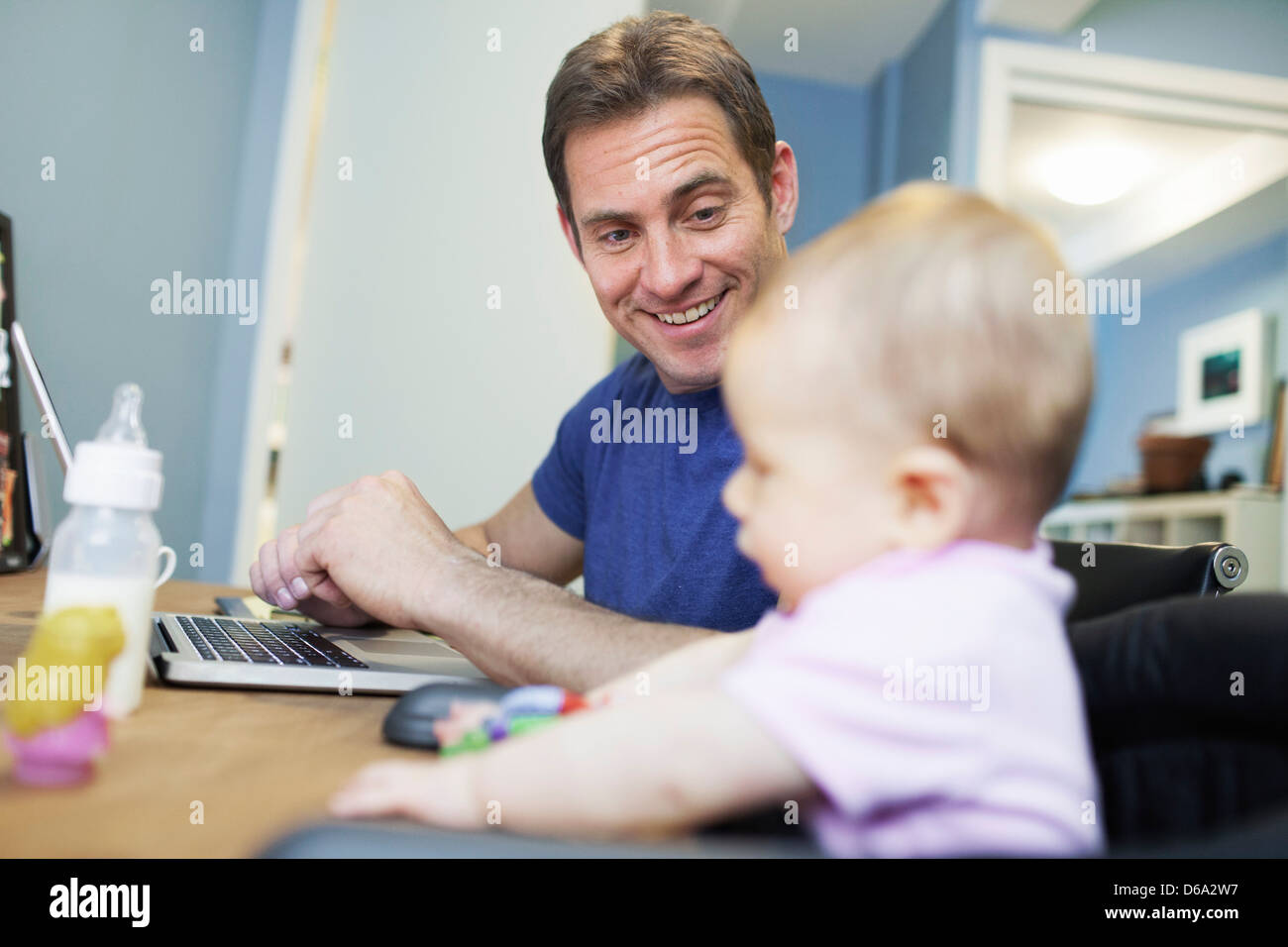Baby girl sitting with father at work - Stock Image