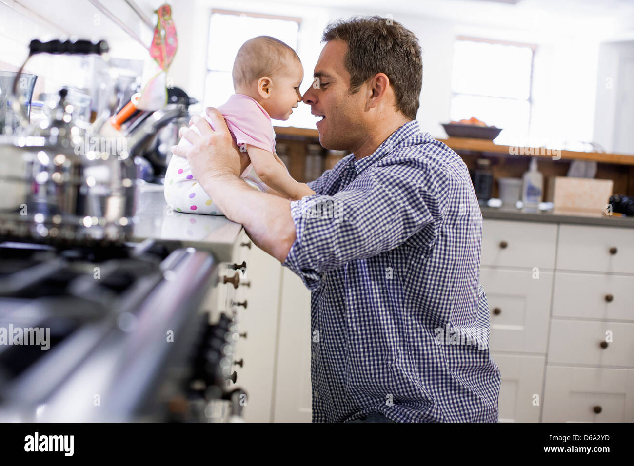 Father with baby daughter in kitchen - Stock Image
