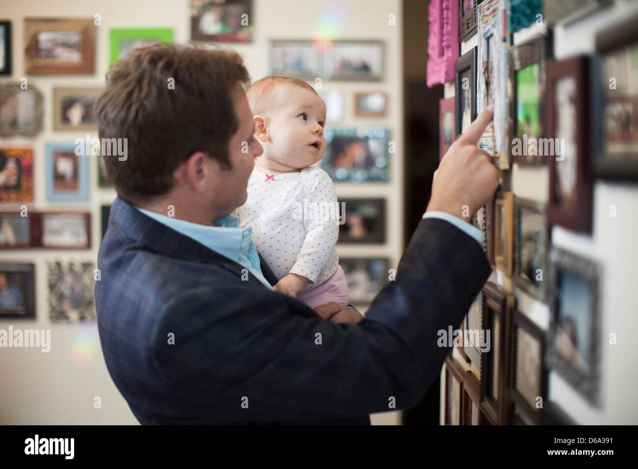 Businessman and baby looking at pictures - Stock Image