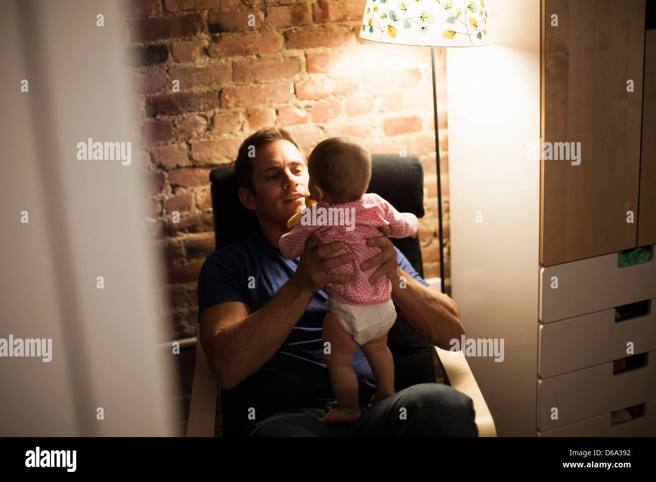 Father holding baby daughter in armchair - Stock Image