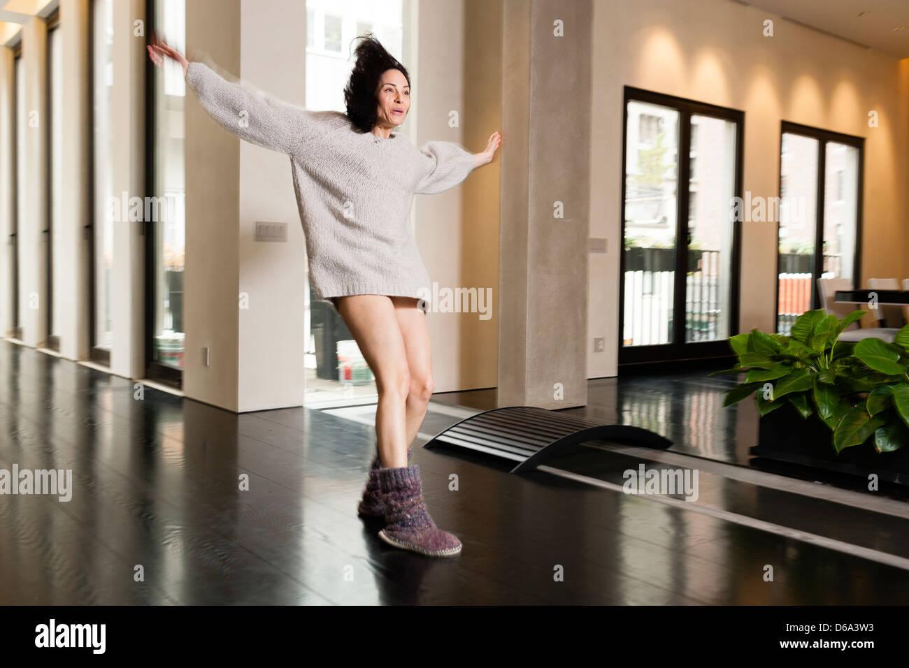 Woman sliding in socks in hallway - Stock Image