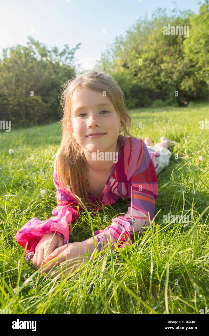 Girl laying in grassy field Stock Photo: 55541697 - Alamy