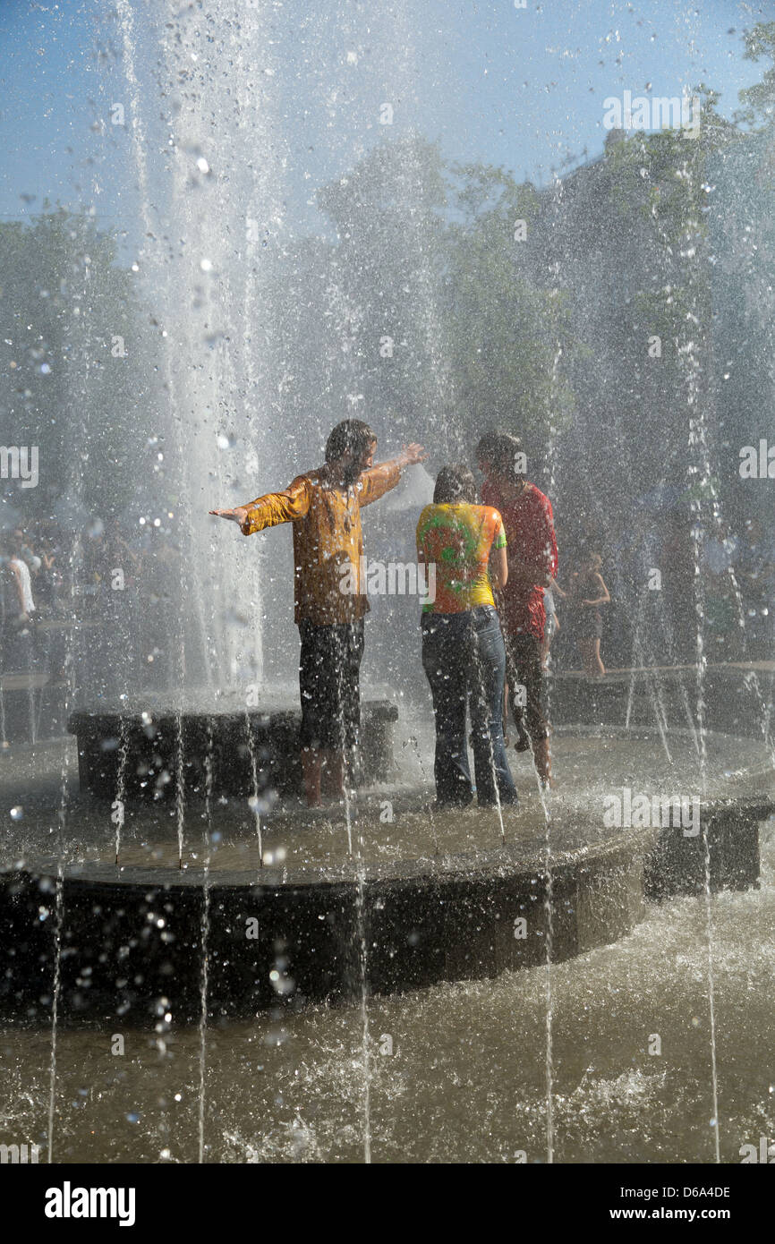 Lviv, Ukraine, adolescents dip in the fountain in front of the Opera - Stock Image