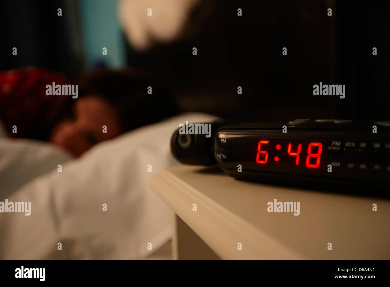 alarm clock early morning with early twenties woman lying in bed in a bedroom - Stock Image