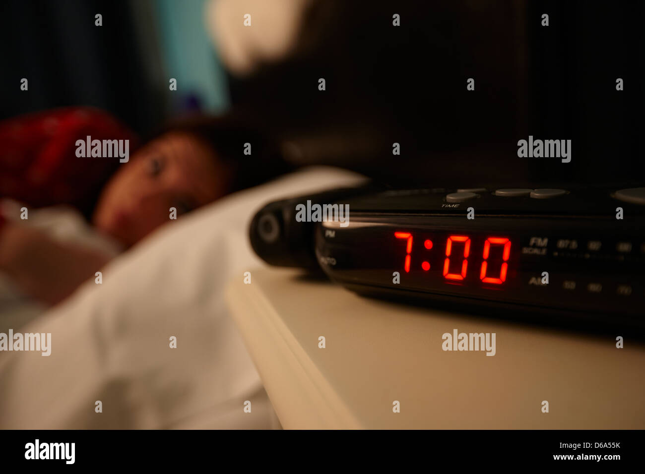 alarm clock early morning with early twenties woman lying in ...