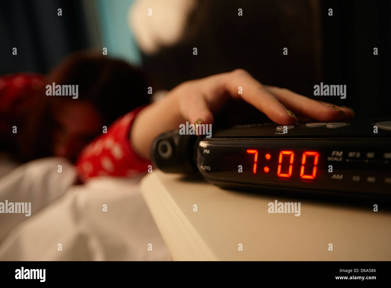 alarm clock early morning with early twenties woman turning off alarm lying in bed in a bedroom - Stock Image