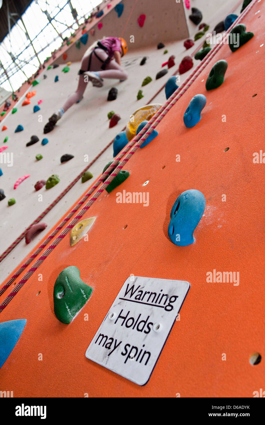 Young children on an indoor climbing wall with warning sign. - Stock Image