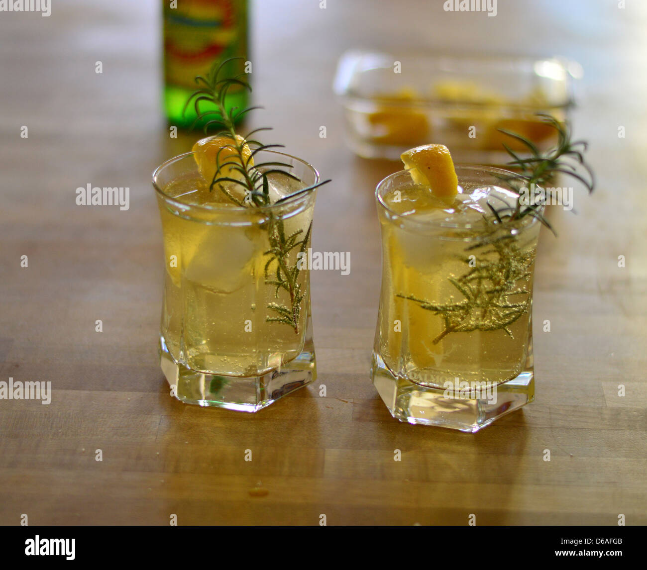 Ginger beer and gin cocktails with sprigs of fresh rosemary and cubes lemons as garnishes Stock Photo